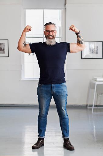 Smiling muscular Caucasian hipster man flexing biceps - gettyimageskorea