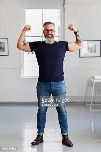 smiling muscular caucasian hipster man flexing biceps - flexing muscles stock pictures, royalty-free photos & images