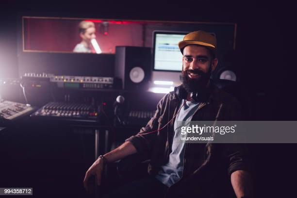 smiling music producer working in recording studio with music artist - editor stock pictures, royalty-free photos & images