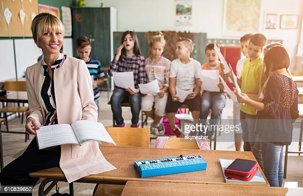 Smiling music teacher with group of children in the classroom.