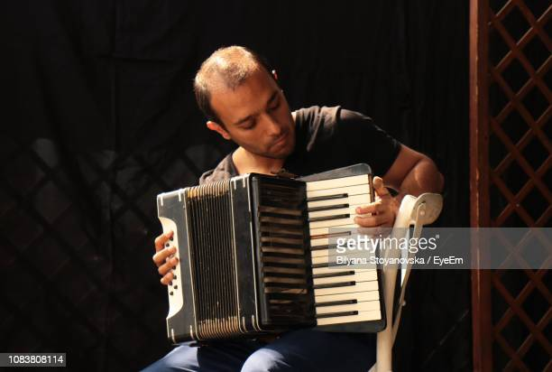 smiling musician playing accordion on stage - accordion stock pictures, royalty-free photos & images