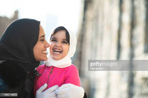 smiling muslim mother and child - emigration and immigration stock pictures, royalty-free photos & images