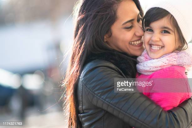smiling muslim mother and child - immigrant stock pictures, royalty-free photos & images