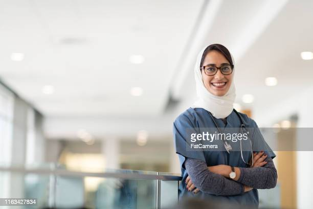 smiling muslim physician standing in a hospital corridor - female doctor stock pictures, royalty-free photos & images