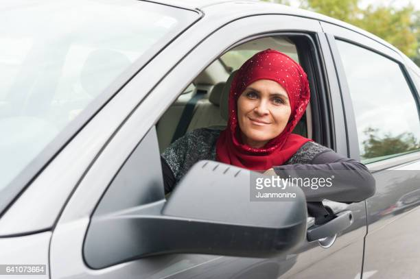 Smiling muslim woman driving