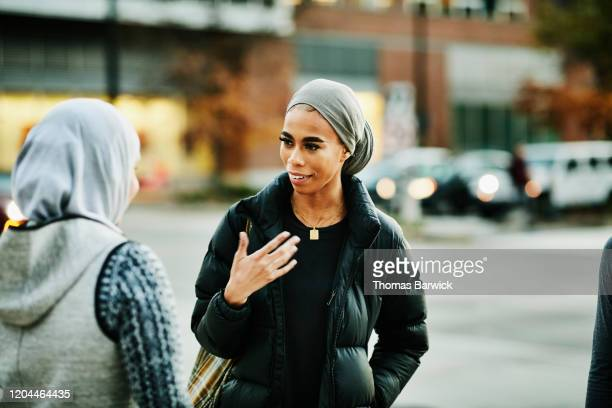 smiling muslim woman in discussion with friend while waiting for ride share - 20 24 years stock pictures, royalty-free photos & images