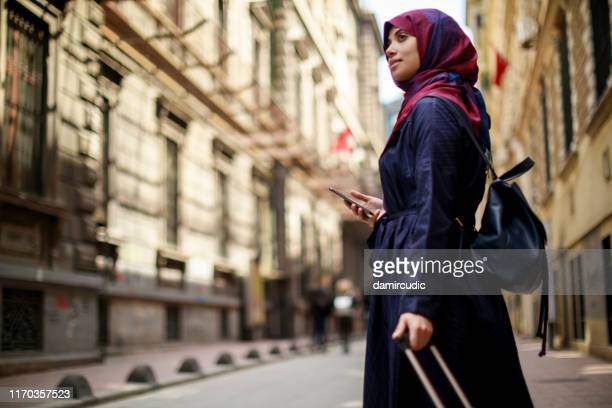 smiling muslim woman travelling - damircudic stock photos and pictures