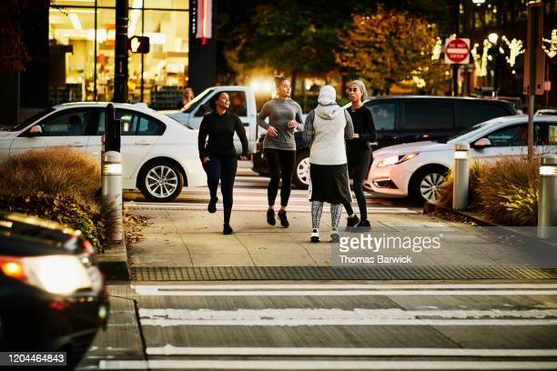 smiling muslim women waiting for crossing light to change while on run after work - walk don't walk signal stock pictures, royalty-free photos & images