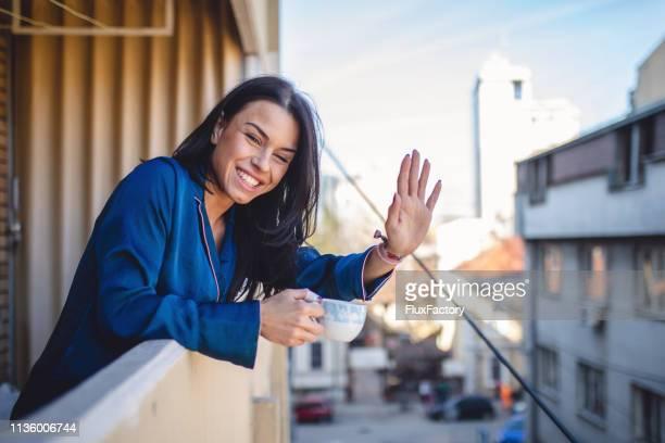 smiling neighbor waving while enjoying a cup of coffee - bella ciao foto e immagini stock