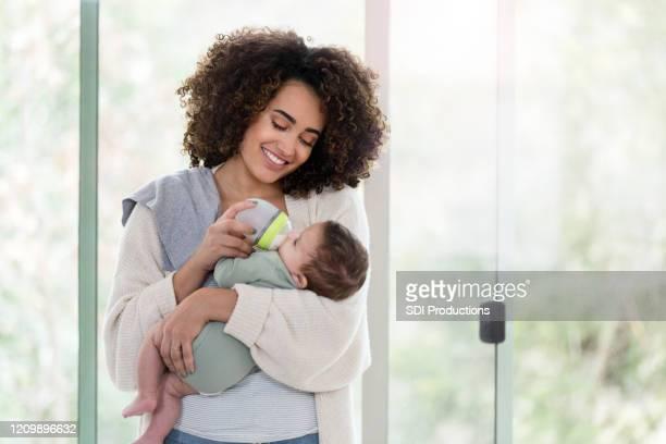 笑顔の新しいママは男の子を養う - 哺乳瓶 ストックフォトと画像
