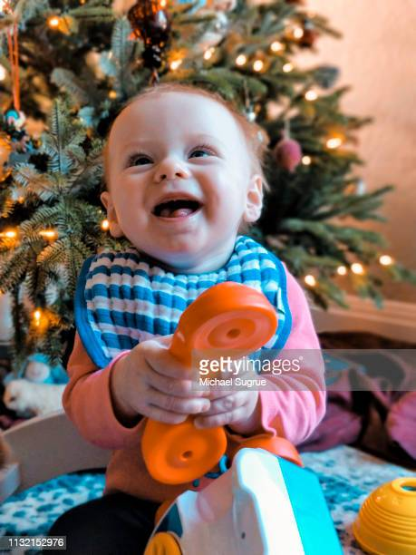 Smiling newborn baby in front of Christmas tree.