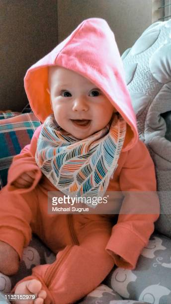 Smiling newborn baby in pink outfit.