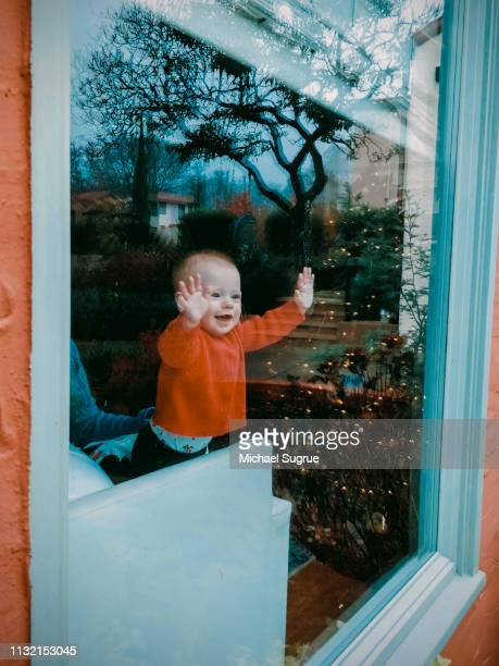 Smiling newborn baby looking out window.