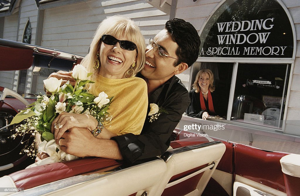 Smiling, Newlywed Couple Sitting in the Front Seat of Their Convertible by a Drive in Church : Stock Photo