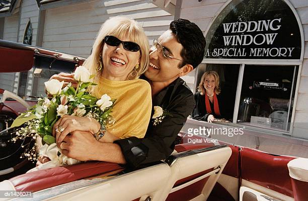 smiling, newlywed couple sitting in the front seat of their convertible by a drive in church - may december romance stock photos and pictures