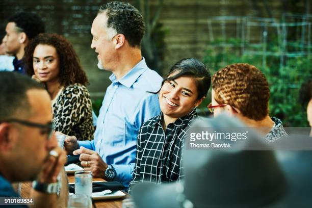 Smiling niece in discussion with aunt during outdoor family dinner party
