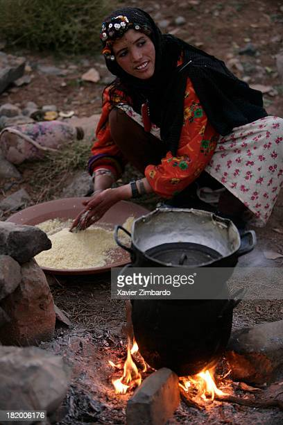 A smiling nomadic woman dressed in traditional clothing prepares a meal with couscous over an open log fire on September 15 2005 in Atlas Mountains...