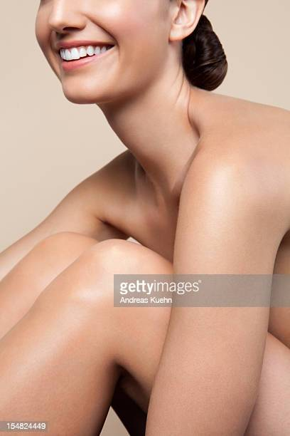 smiling nude young woman hugging legs, cropped. - セミヌード ストックフォトと画像