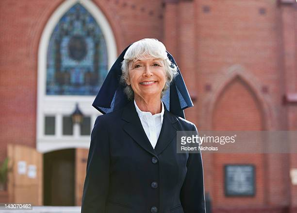 smiling nun walking outdoors - catholicism stock pictures, royalty-free photos & images
