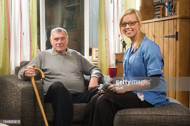 smiling nurse and elderly man - nhs staff stock pictures, royalty-free photos & images