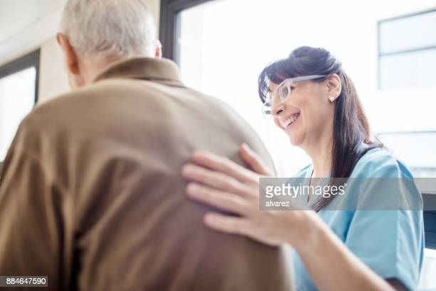 smiling nurse assisting senior man in hospital - accudire foto e immagini stock