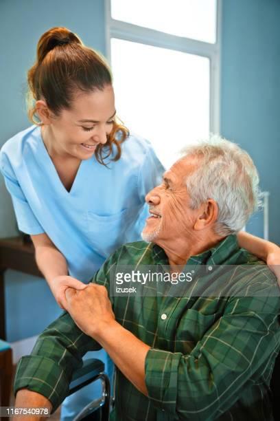 mãos de sorriso da terra arrendada da enfermeira do homem deficiente - izusek - fotografias e filmes do acervo