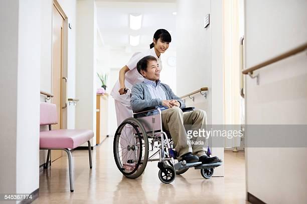 Smiling nurse pushing senior man sitting on wheelchair at hospit