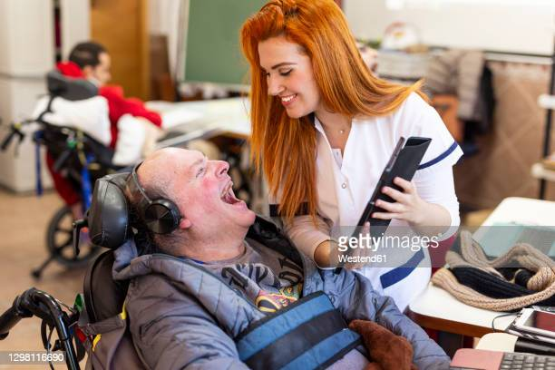 smiling nurse showing digital tablet to happy disabled man in nursing home - persons with disabilities stock pictures, royalty-free photos & images