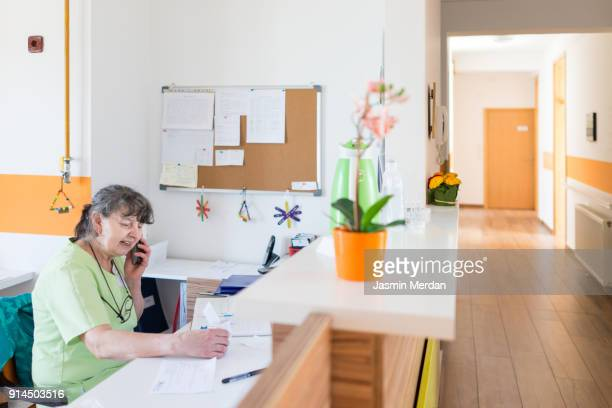smiling nurse sitting at desk and answering phone - medical receptionist uniforms stock photos and pictures