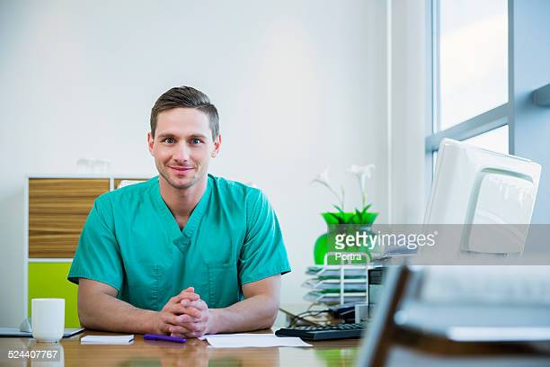 Smiling nurse sitting at desk in clinic