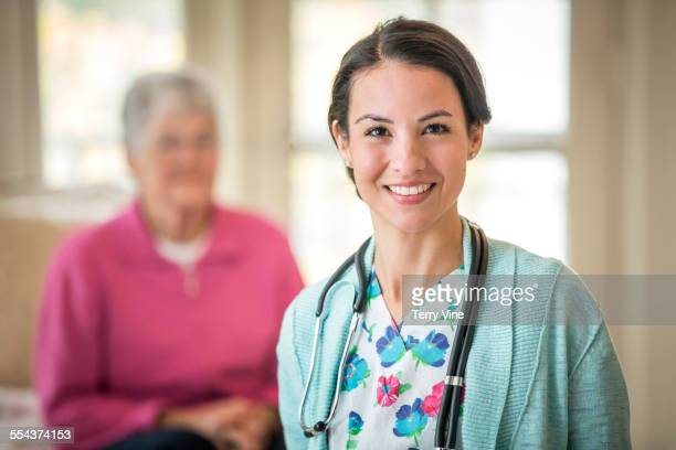 Smiling nurse standing in home with patient