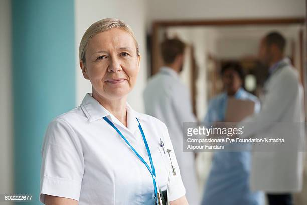 Smiling nurse standing in hospital corridor