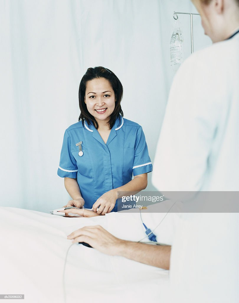 Smiling Nurse Stands by a Patient's Bed, Adjusting the Intravenous Drip : Stock Photo