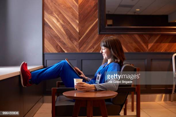 smiling nurse using digital tablet in employee lounge - blue shoe stock pictures, royalty-free photos & images