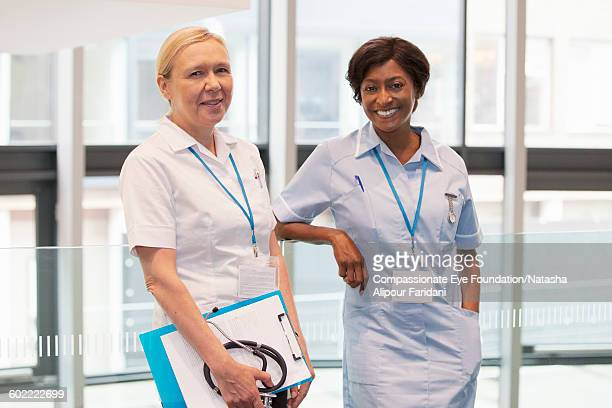 Smiling nurses standing in hospital corridor
