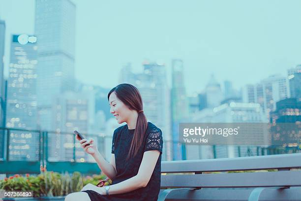 smiling office lady looking at smartphone in city - yiu yu hoi stock pictures, royalty-free photos & images