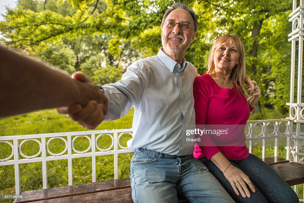 Smiling old couple greeting someone in the park stock photo getty smiling old couple greeting someone in the park stock photo m4hsunfo