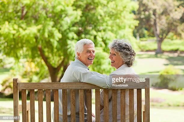 Lächelnd altes Paar Blick zurück auf einer Bank sitzend