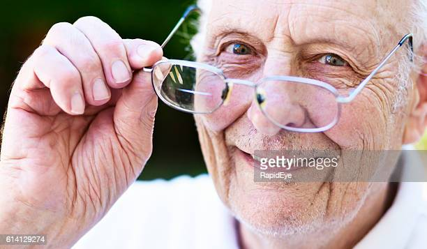 Smiling old man, vision corrected, looks over his spectacles