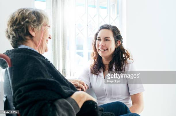 Smiling old woman in wheelchair with friendly attendant