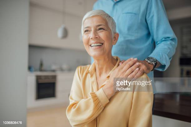 smiling old woman with a hand on her shoulder - hand on shoulder stock pictures, royalty-free photos & images