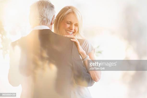 Smiling older Caucasian couple dancing