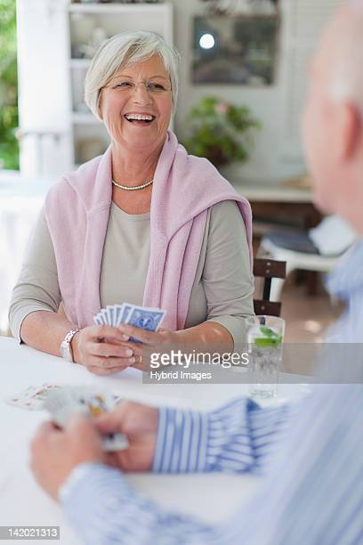 Smiling older couple playing cards