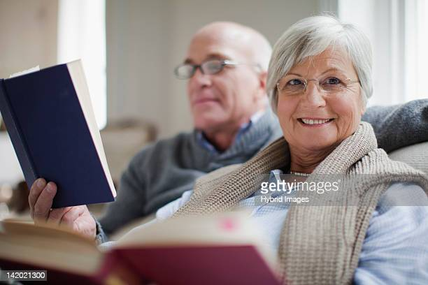 smiling older couple reading books - 50 59 jaar stockfoto's en -beelden