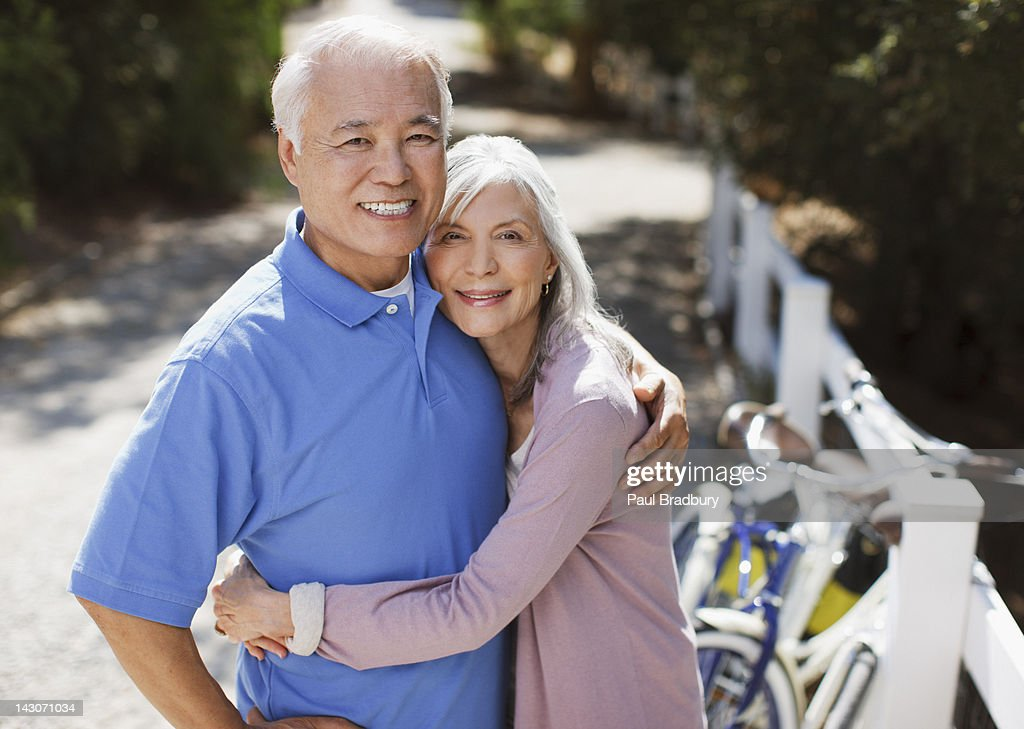 Smiling older couple relaxing outdoors : Stock Photo