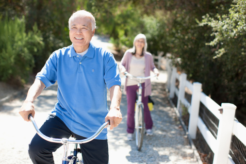 Smiling older couple riding bicycles - gettyimageskorea