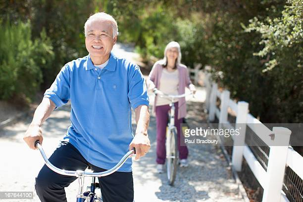 smiling older couple riding bicycles - japanese old man stock pictures, royalty-free photos & images
