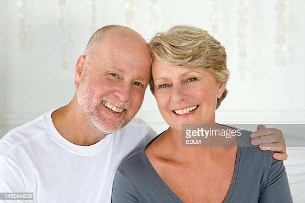 smiling older couple sitting on bed - 50 59 years stock pictures, royalty-free photos & images