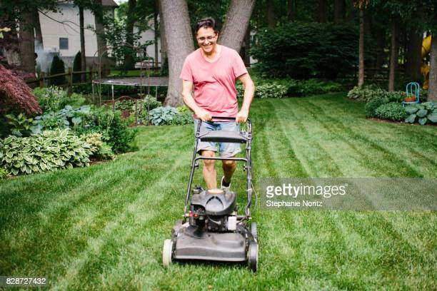 Smiling older man mowing the lawn in a backyard