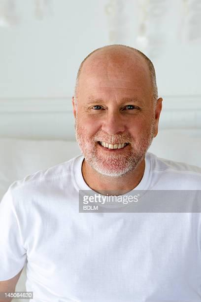 smiling older man sitting on sofa - 55 59 jaar stockfoto's en -beelden